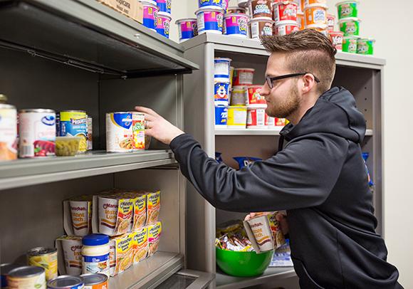 Image of senior Joshua DeMarsh helps stock shelves in Campus Food Pantry